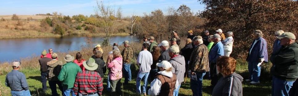 members of the public at a field day presentation near a pond