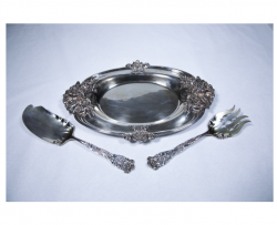 a plate, spoon, and fork from the silver set with a wild rose as part of the silver detail