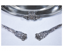 a close up view of a plate and the handles of two utensils from the silver set with a wild rose as part of the silver detail